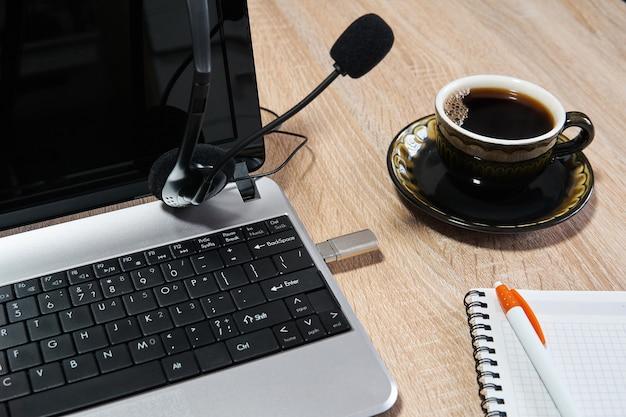 Ordinateur portable, casque avec microphone, ordinateur portable avec stylo et tasse à café sur la table en gros plan