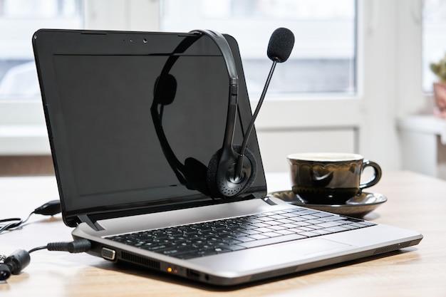 Ordinateur portable, casque avec microphone et tasse à café sur la table en gros plan