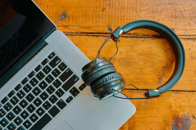 Ordinateur portable et casque sans fil sur table en bois espace de travail de gadgets modernes de freelance mise à plat de pas...