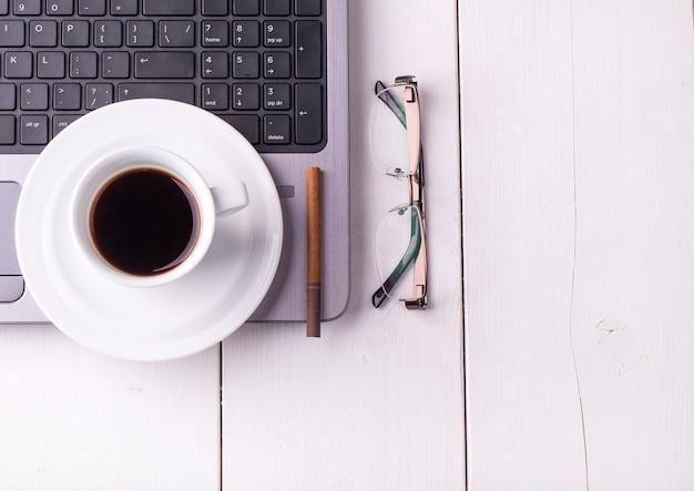 Ordinateur portable, cigarette, verres et une tasse de café sur une table en bois blanche