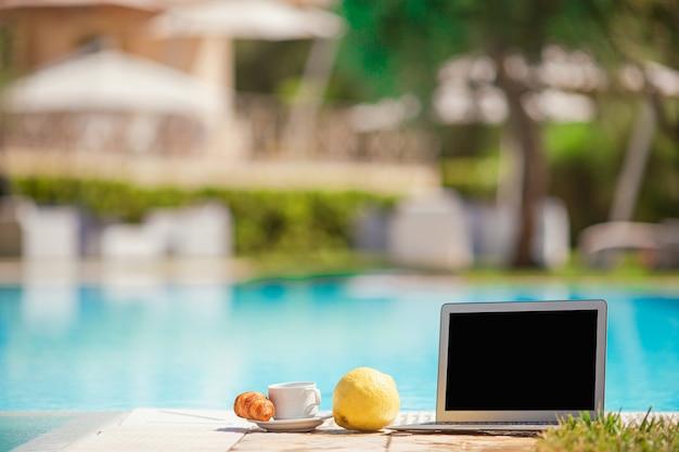 Ordinateur portable, citron, café et croissant au bord de la piscine