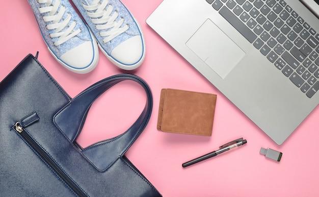 Ordinateur portable, clé usb et accessoires féminins à la mode sur fond rose: sac, portefeuille, baskets, sac. vue de dessus. mise à plat.