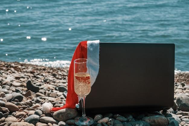 Un ordinateur portable et une coupe de champagne, un chapeau de noël rouge au bord de la mer. concept de célébration du nouvel an.