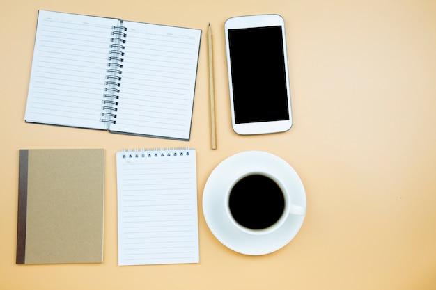 Ordinateur portable couverture brune téléphone portable calculatrice café noir tasse blanche horloge verte