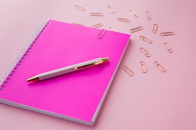 Ordinateur portable avec couverture en plastique de couleur rose, stylo et trombones. fond rose. mise au point sélective