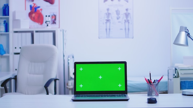 Ordinateur portable dans une armoire d'hôpital avec écran vert et infirmière portant un uniforme bleu tenant un masque de protection. ordinateur portable avec écran remplaçable en clinique médicale.