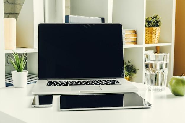 Ordinateur portable dans une salle lumineuse sur une table de travail avec des fournitures de bureau