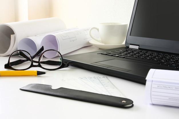 Un ordinateur portable dispose d'un rouleau de papier placé sur le bureau.