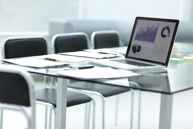 Ordinateur portable avec données financières à l'écran et presse-papiers sur la table chez l'homme d'affaires