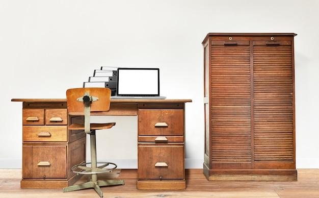 Ordinateur portable et dossier posé sur un bureau vintage