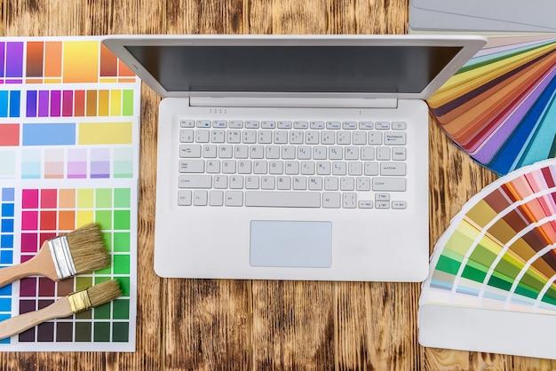 Ordinateur portable avec des échantillons de couleur sur une table en bois pour la rénovation domiciliaire