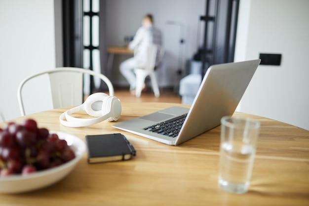 Ordinateur portable, écouteurs, verre d'eau, raisins frais et cahier sur table