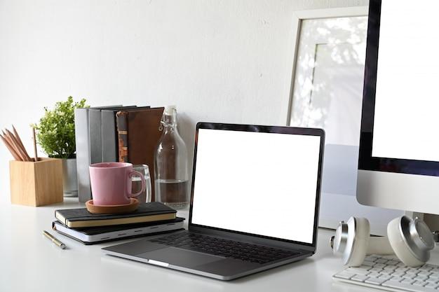 Ordinateur portable écran blanc avec affiche vierge et fournitures de bureau.