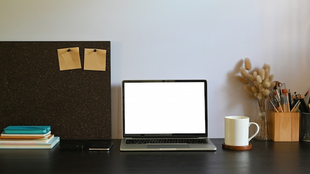 Un ordinateur portable à écran blanc blanc met sur un bureau de travail noir entouré d'accessoires
