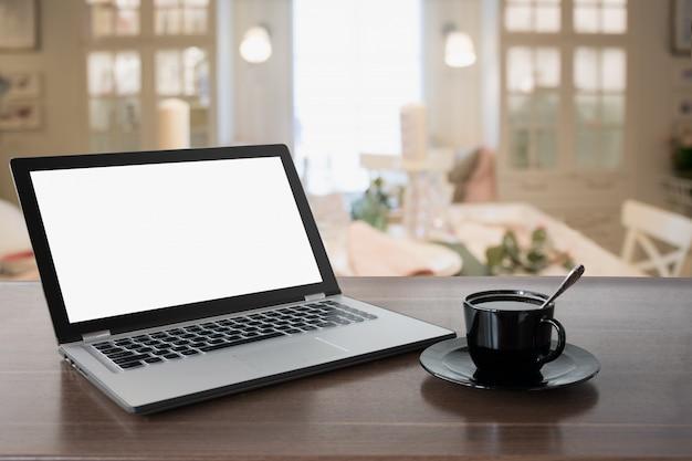 Ordinateur portable avec écran blanc et café sur la table