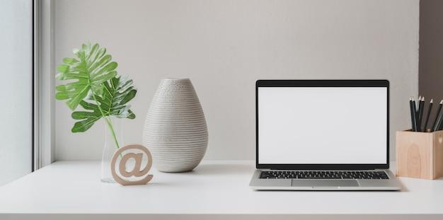 Ordinateur portable à écran blanc dans un espace de travail minimal avec pot d'arbre, vase en céramique et espace de copie