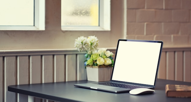 Ordinateur portable à écran blanc dans un lieu de travail confortable et moderne