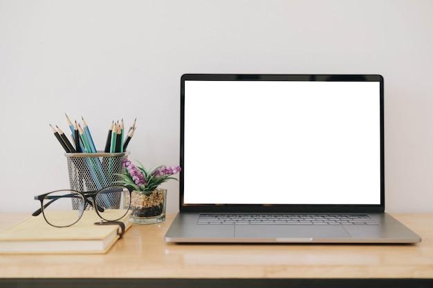 Ordinateur portable à écran blanc et fond d'espace de travail affiche dans un bureau moderne