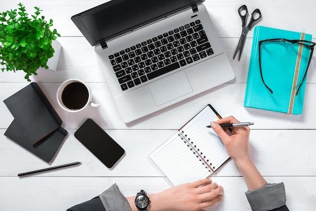 Ordinateur portable avec écran blanc et mains de la fille. espace de travail plat, vue de dessus. copier l'espace