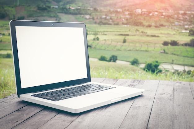 Ordinateur portable écran blanc sur la nature pittoresque de fond, bureau extérieur.