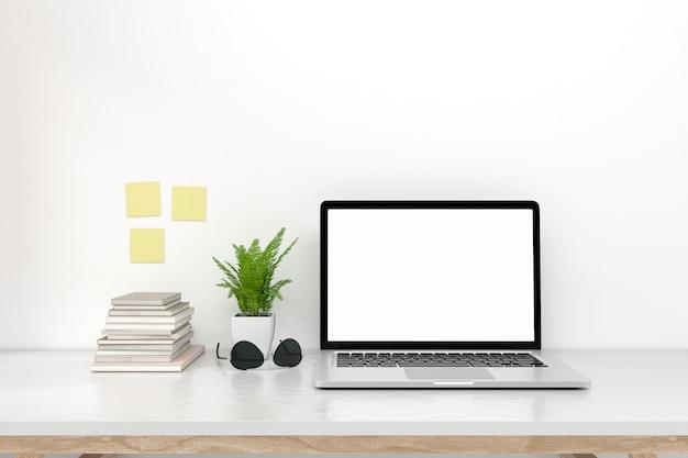 Ordinateur portable à écran blanc avec une note collante sur le bureau de l'espace de travail