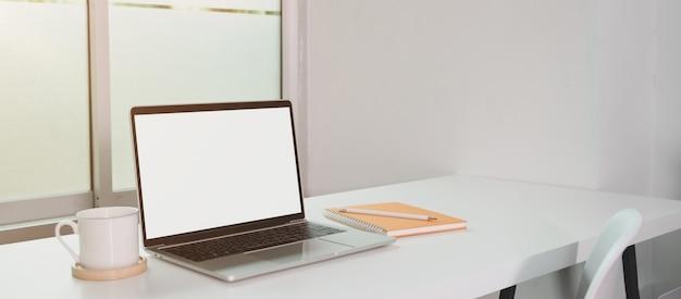 Ordinateur portable à écran blanc ouvert avec une tasse de café