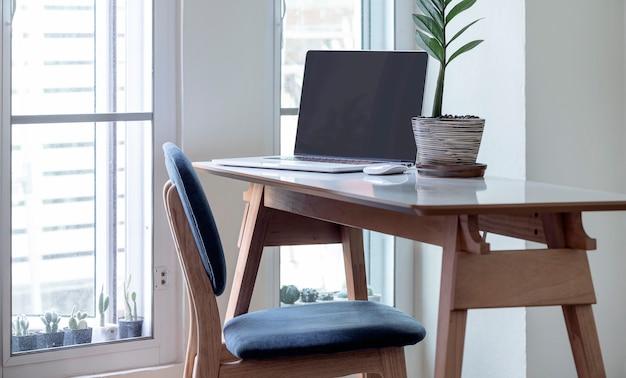 Ordinateur portable à écran blanc sur une table en bois dans une maison moderne.