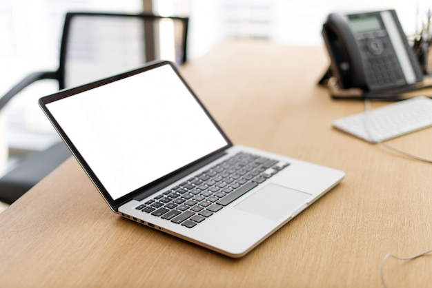 Ordinateur portable avec écran blanc sur table en bois et fond flou