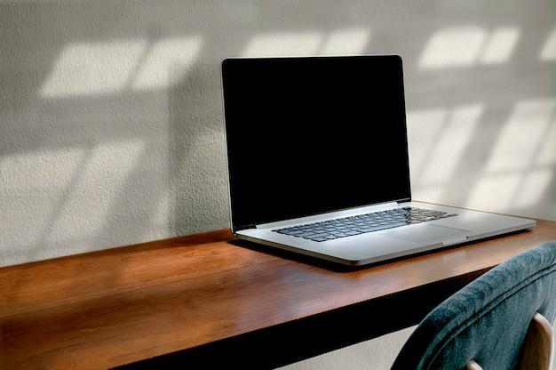 Ordinateur portable avec écran blanc sur table de comptoir en bois dans le salon, copiez l'espace.