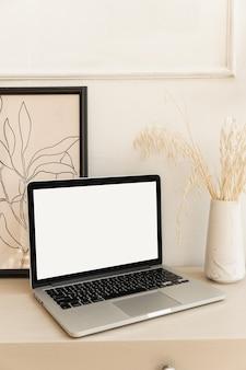 Ordinateur portable avec écran blanc sur table avec décorations boho