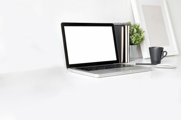 Ordinateur portable à écran blanc sur une table de travail blanche