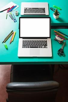 Ordinateur portable avec un écran blanc sur une table turquoise avec une chaise à proximité