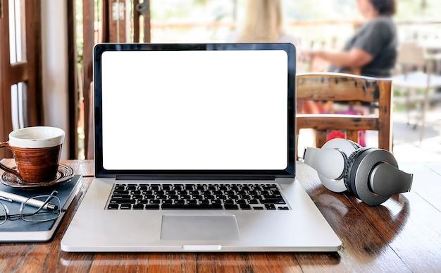 Ordinateur portable avec un écran blanc vide sur une table en bois dans le café-restaurant.