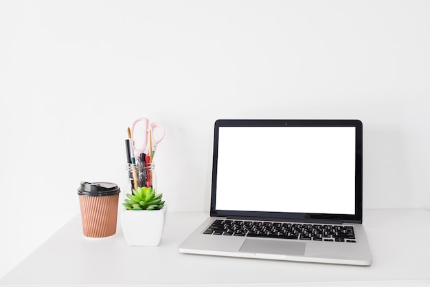 Ordinateur portable avec écran blanc vierge et tasse de disposition sur le bureau