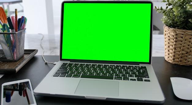 Ordinateur portable avec écran vert pour remplacement avec arrière-plan flou