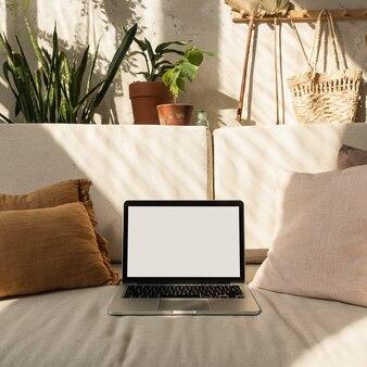 Ordinateur portable avec écran vide sur un canapé confortable dans les ombres chaudes du soleil.