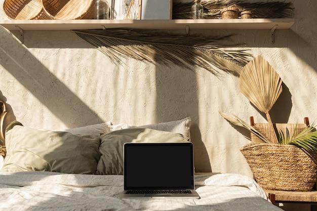 Ordinateur portable à écran vide. ombres chaudes du soleil sur le mur. ambiance parisienne. design d'intérieur de maison de style bohème chaleureux