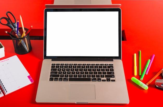 Un ordinateur portable avec un écran vide avec des papeteries sur une table rouge