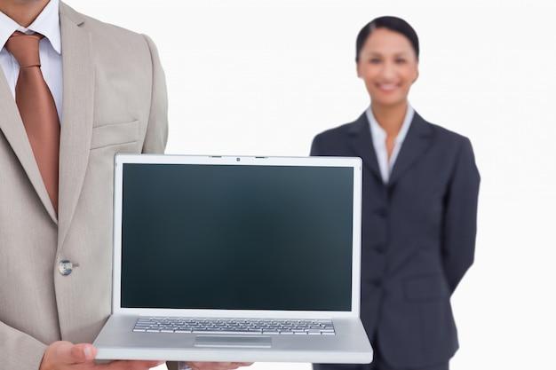 Un ordinateur portable est présenté par un vendeur avec un collègue derrière lui