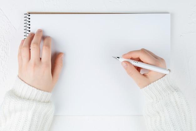 Ordinateur portable avec feuille vide sur un mur blanc avec un stylo dans les mains, vue de dessus. mise à plat avec espace de copie.