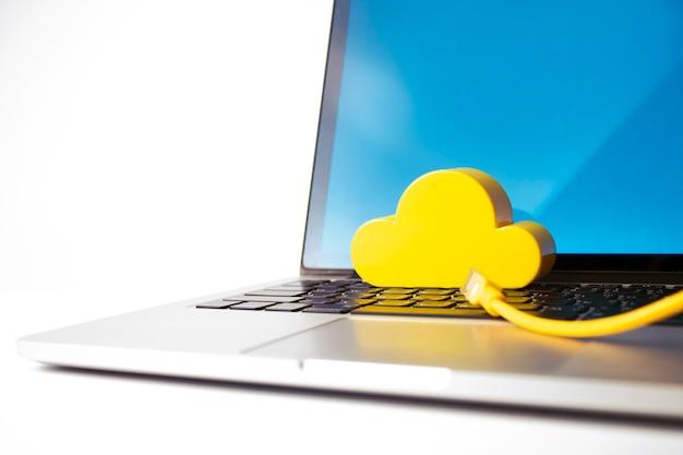 Ordinateur portable avec fil lan et nuage jaune dans le réseau d'entreprise internet