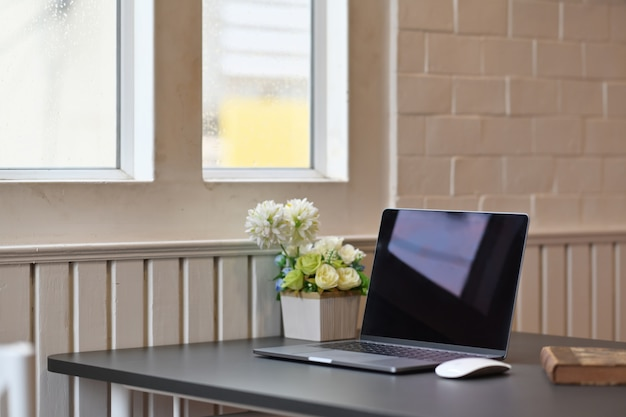 Ordinateur portable avec des fournitures de bureau et des gadgets sur une table en bois