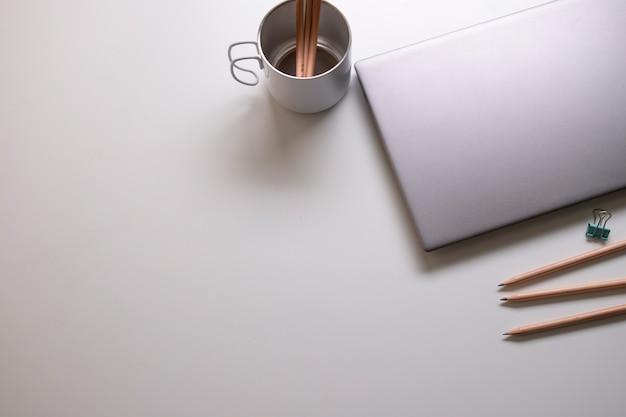 Ordinateur portable et fournitures de bureau sur la table blanche