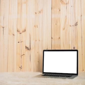 Ordinateur portable sur une fourrure douce contre une planche de bois
