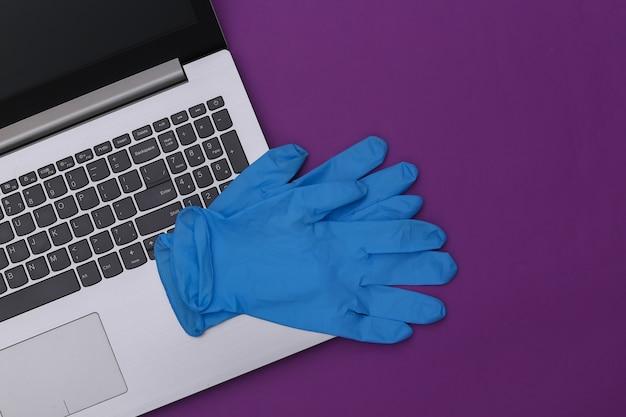 Un ordinateur portable avec des gants chirurgicaux sur fond violet. vue de dessus