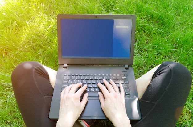 Ordinateur portable sur les genoux de la fille sur l'herbe verte
