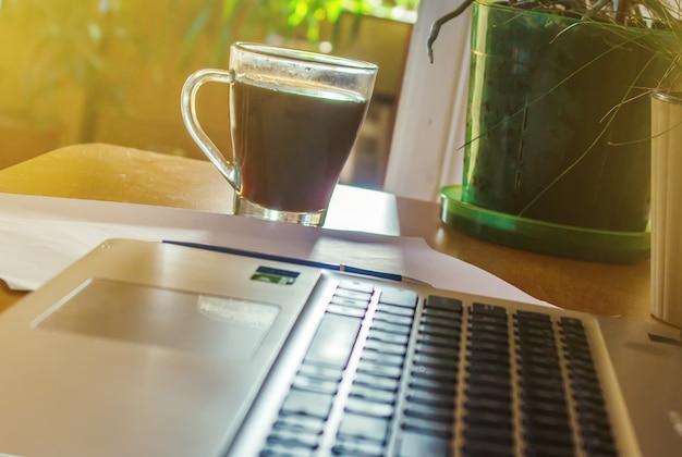 Ordinateur portable gros plan d'un clavier et d'une tasse de café chaud le matin. mise au point sélective.