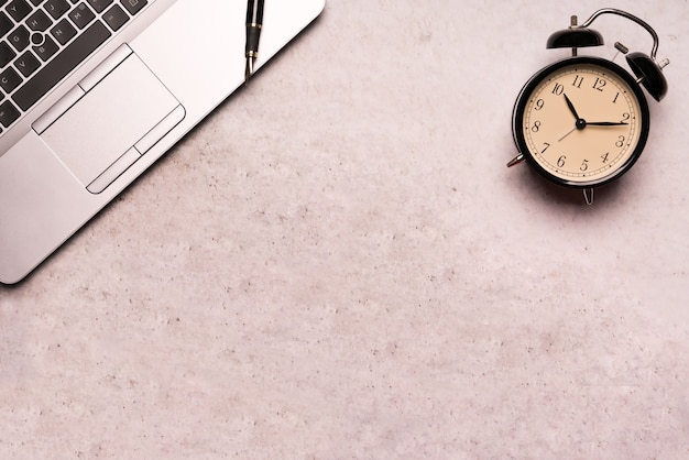 Ordinateur portable avec horloge noire sur la table de travail plat poser la vue de dessus de composition