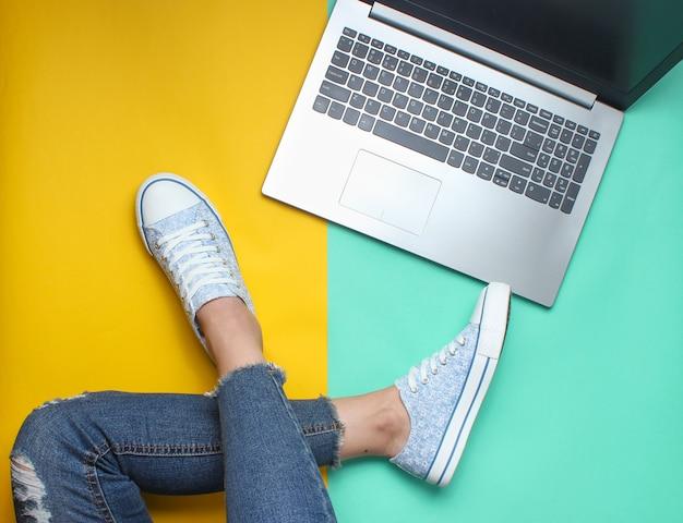 Ordinateur portable, jambes féminines en jeans et baskets, style plat