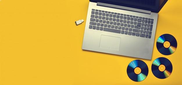 Ordinateur portable, lecteurs de cd, clé usb sur une surface jaune.